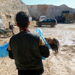 Un hombre carga el cadáver de un niño en Idlib, Siria (Reuters)