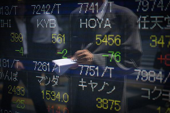 Hombre toma notas frente a tablero de la Bolsa de Tokio