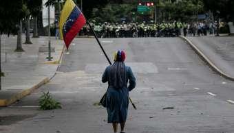 Manifestante ondea bandera de Venezuela frente a columna de policías