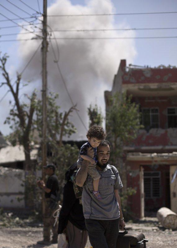 Nino es cargado por su padre en Mosul