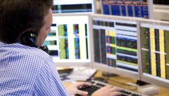 Un operador de la Bolsa de Londres realiza una negociación telefónica