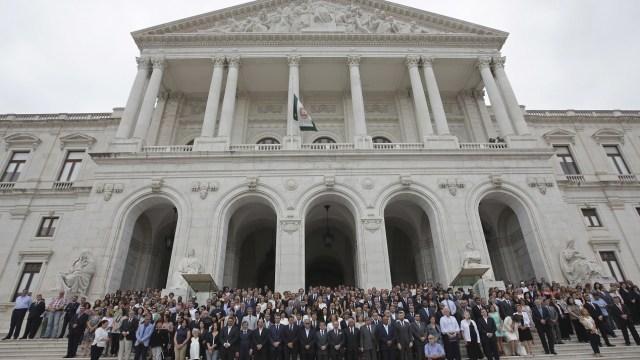 El primer ministro portugués, Antonio Costa, se une a los miembros del gobierno y los legisladores en los escalones del edificio del Parlamento en Lisboa (AP)