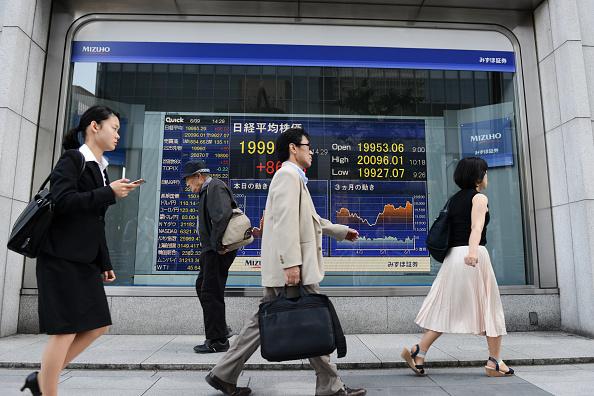 Peatones frente a tablero de la Bolsa de Tokio