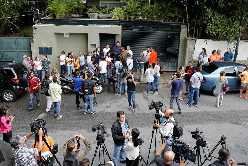Gente y periodistas se reúnen en la entrada de la casa del líder opositor de Venezuela, Leopoldo López (Reuters)