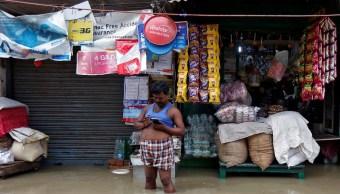 Hombre revisa telefono celular calle llena agua lluvia Kolkata India