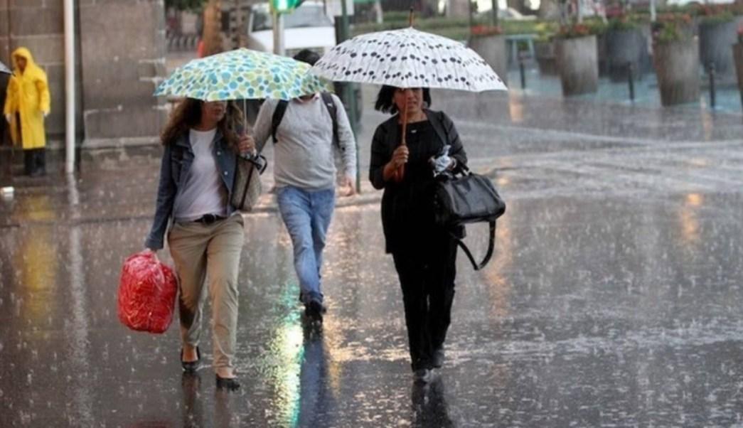 Foto: Dos mujeres se protegen de la lluvia, 14 julio 2019