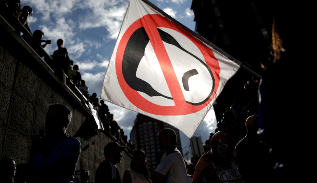 Opositores portan cartel con caricatura de Maduro
