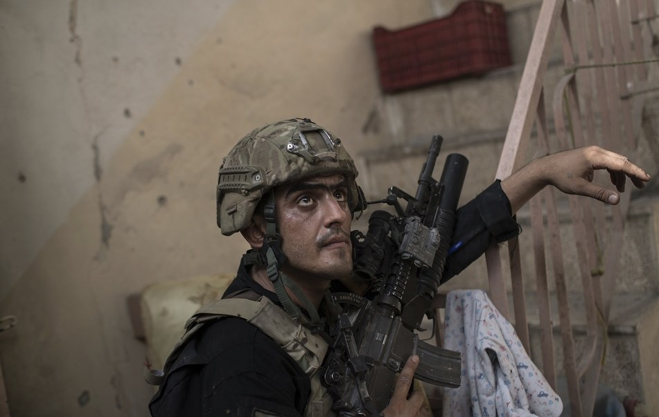 Un soldado de las Fuerzas Especiales Iraquíes vigila a los militantes del Estado Islámico en Mosul, Irak (AP)