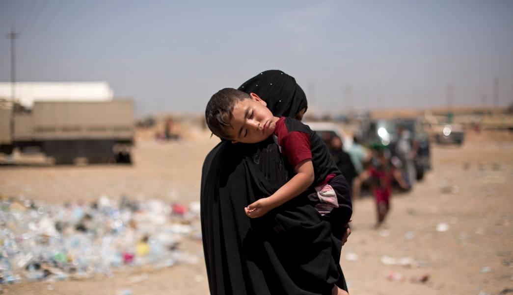 Mujer con hijab carga a nino dormido tras huir de Mosul