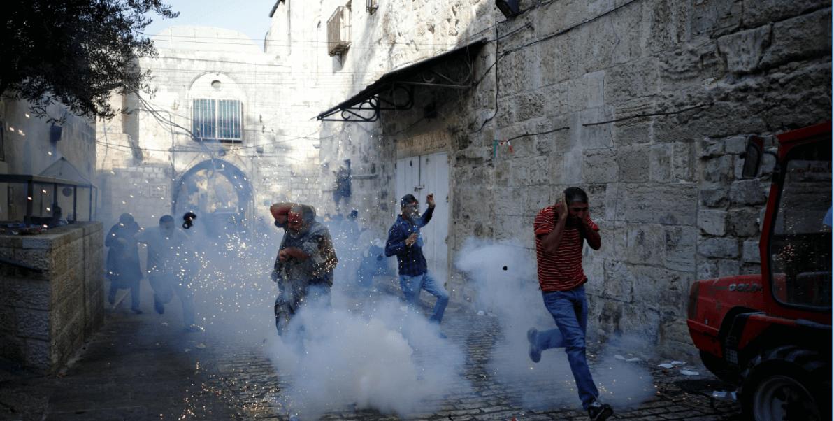 Palestinos corren luego de la explosión de una granada en la Explanada de las Mezquitas
