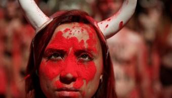 Manifestantes de derechos de los animales gritan consignas con polvo rojo previo a la famosa corrida de los toros de San Fermín en Pamplona (Reuters)