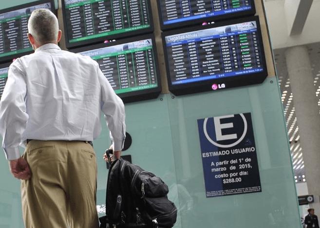 Pasajero revisa tableros de horarios en el AICM