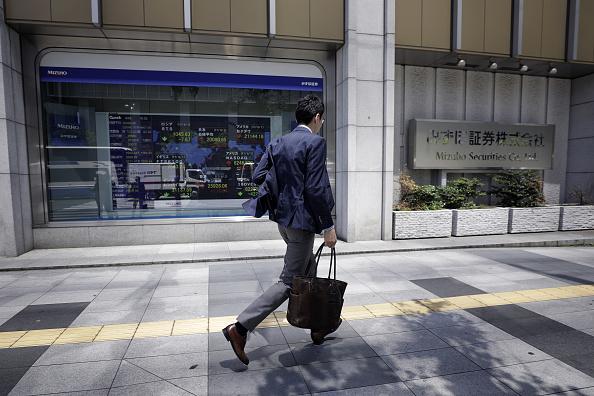 Peatón pasa junto a una firma de valores en Tokio