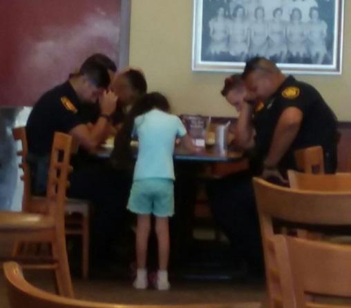 Una niña reza con agentes de policía de San Antonio, Texas (Foto: Facebook Martha Bosquez)