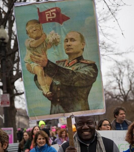 Una pancarta del presidente Putin que sostiene a un bebé con una imagen sobrepuesta de Donald Trump durante una protesta en EU (Getty Images)