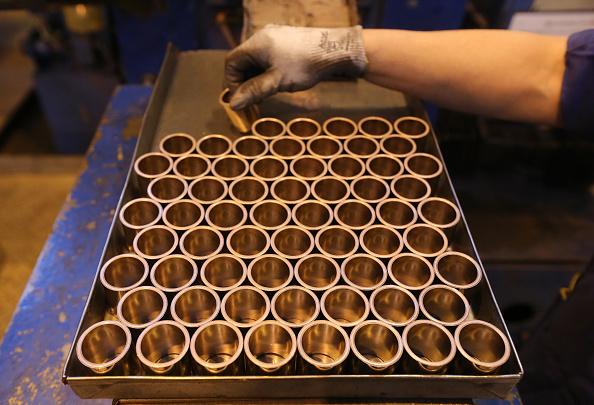 Un trabajador prepara una bandeja de anillos de cobre