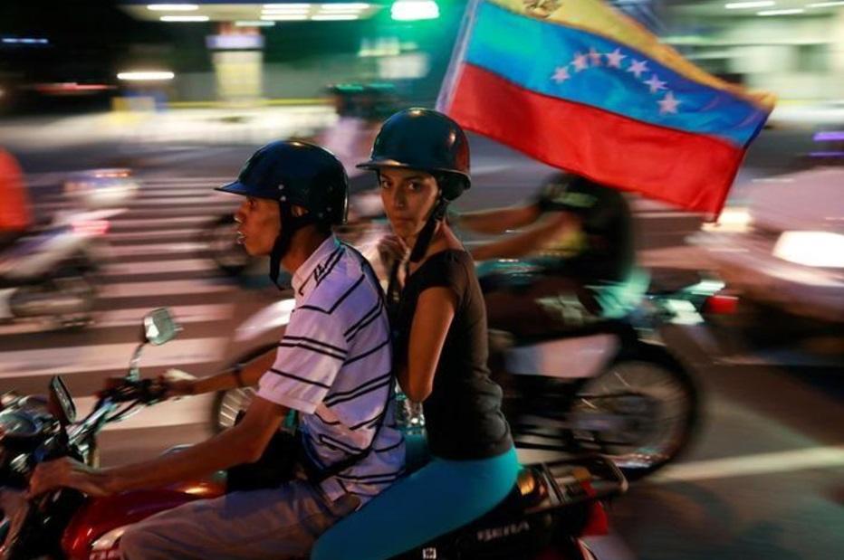 Partidarios de la oposición montan en una motocicleta después de un plebiscito no oficial contra el gobierno del presidente Nicolás Maduro (Reuters)