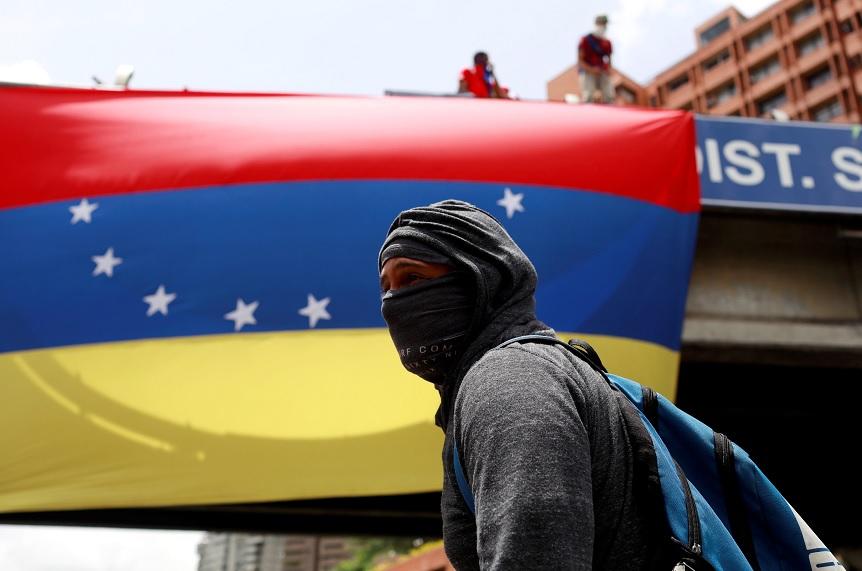 Un manifestante camina frente a una bandera nacional de Venezuela durante una protesta contra el presidente venezolano Maduro en Caracas (Reuters)