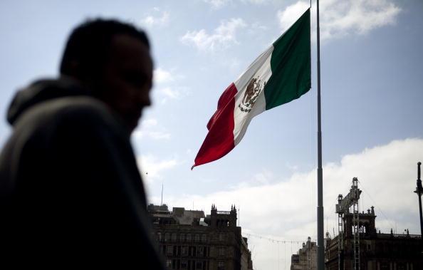 Hombre pasa junto a la bandera mexicana en el Zócalo