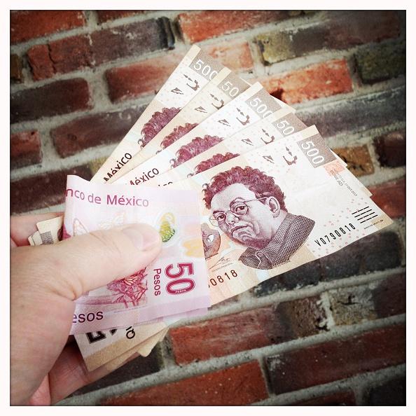 Un hombre sostiene billetes de 500 y 50 pesos