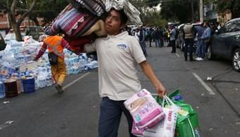 Voluntario transporta víveres