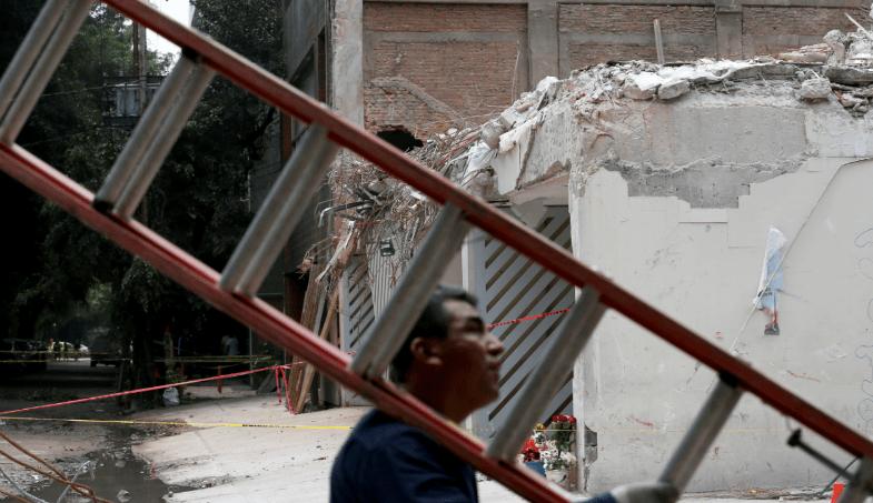 Voluntario carga escalera en zona de derrumbe de la CDMX