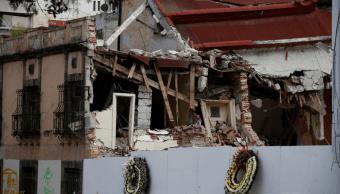 Coronas fúnebres frente a escombros del laboratorio colapsado tras sismo del 19S