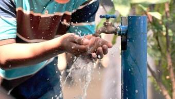 Un joven toma agua potable de la llave