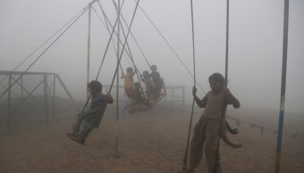 En India, niños juegan en medio de una fuerte contaminación