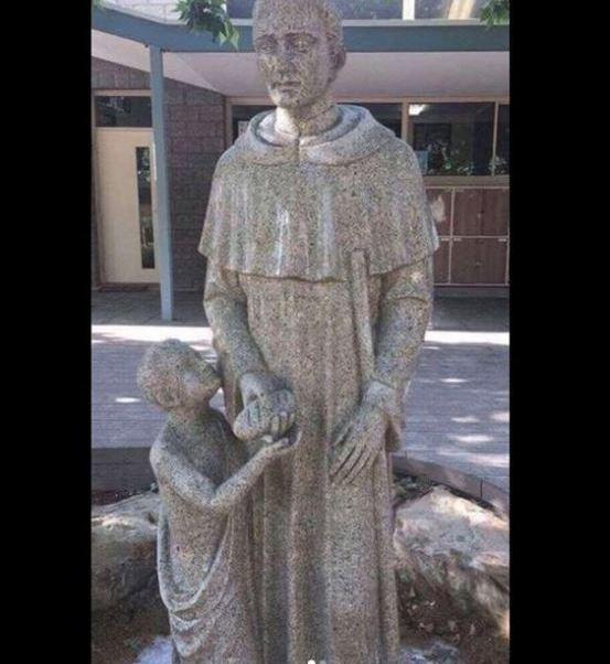 Una escuela católica en Australia cubre la estatua de un fraile que sostiene un pan, que recibe un niño, por supuesta connotación sexual. (Shitadelaide/Instagram)