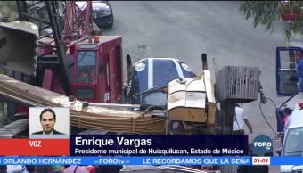 Retroexcavadora cae encima de vehículos en Huixquilucan