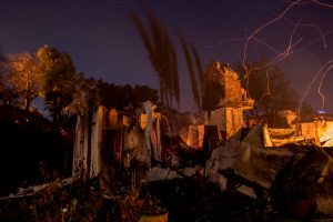 SUNLAND, CA - DECEMBER 05: Strong wind blows embers across the smoldering ruins of a house at the Creek Fire on December 5, 2017 in Sunland, California. Strong Santa Ana winds are rapidly pushing multiple wildfires across the region, expanding across tens of thousands of acres and destroying hundreds of homes and structures. (Photo by David McNew/Getty Images)