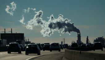 Vehículos circulan en Nueva Jersey mientras una fábrica emite humo