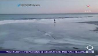 Hombre patina en hielo a la orilla del mar en Nueva York