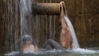 Paquistaníes bañándose por ola de calor. (AP, archivo)