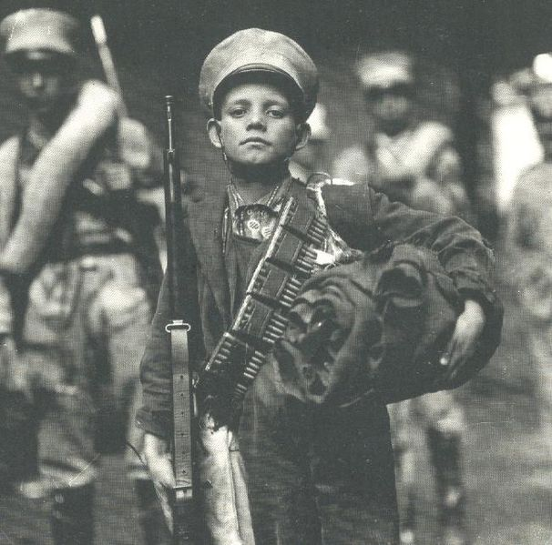 nino-soldado-revolucion-mexicana-sostiene-rifle-canana-municion-principios-siglo-xx