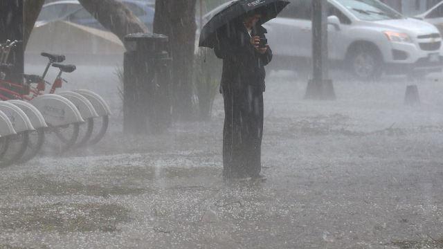 foto:Una persona se protege de la fuerte lluvia, 6 julio 2019