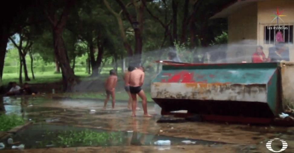 Niños migrantes se bañan con mangueras prestadas en Huixtla, Chiapas