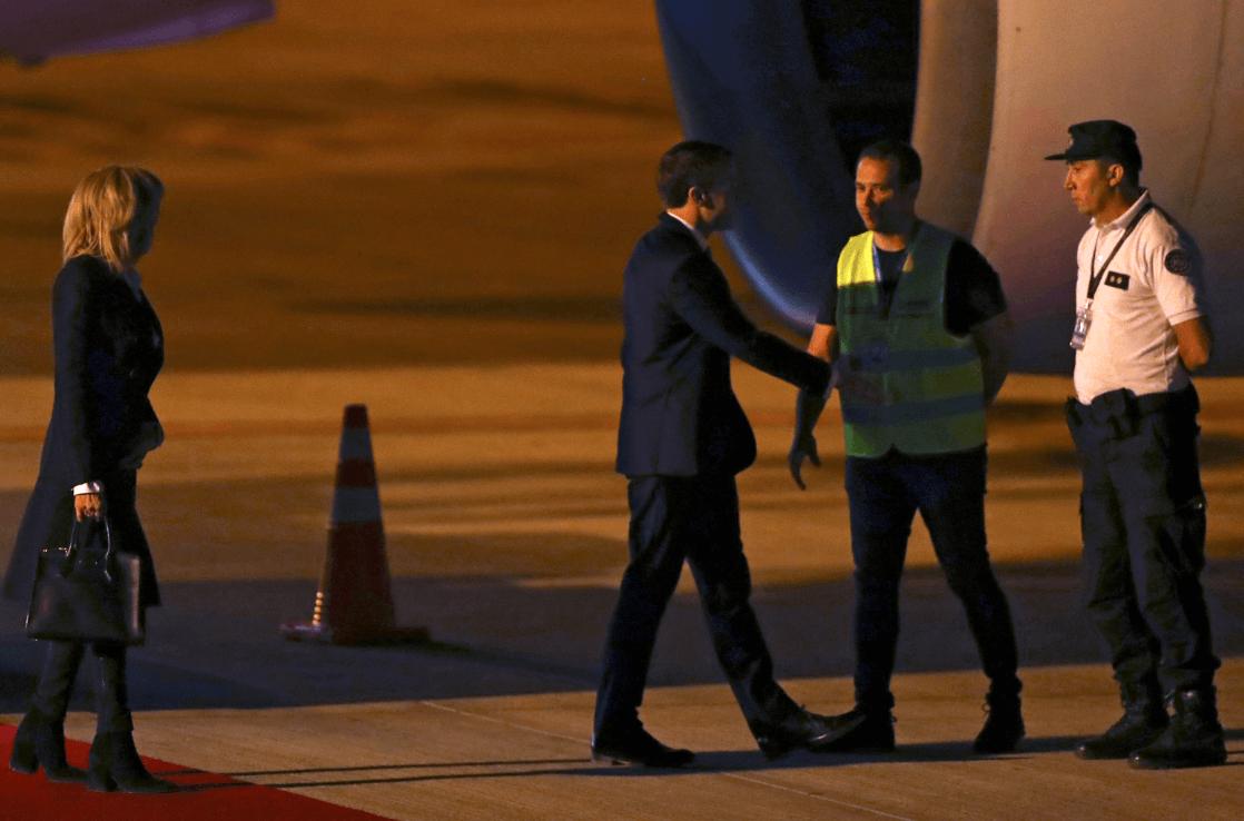 Empleados del aeropuerto reciben a Macron, ante el retardo de la vicepresidenta. (Reuters)