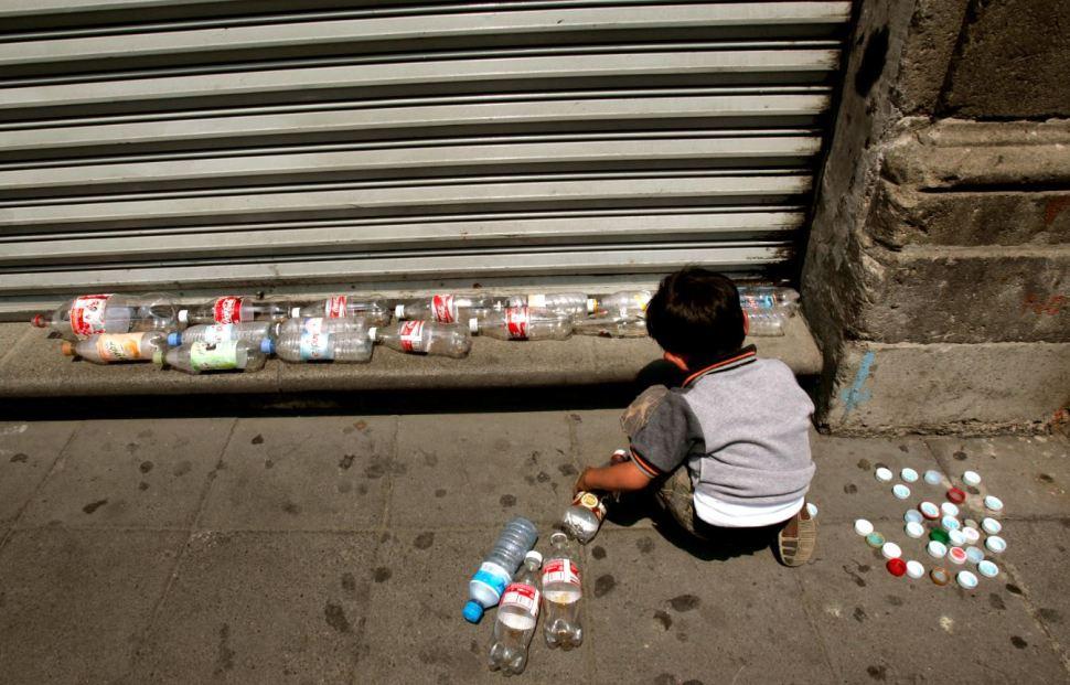 Niño juega con botellas de plástico vacías en el centro de la Ciudad de México (AP Images)