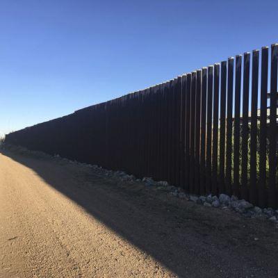 Migrantes marchan en silencio para protestar contra el muro fronterizo con México