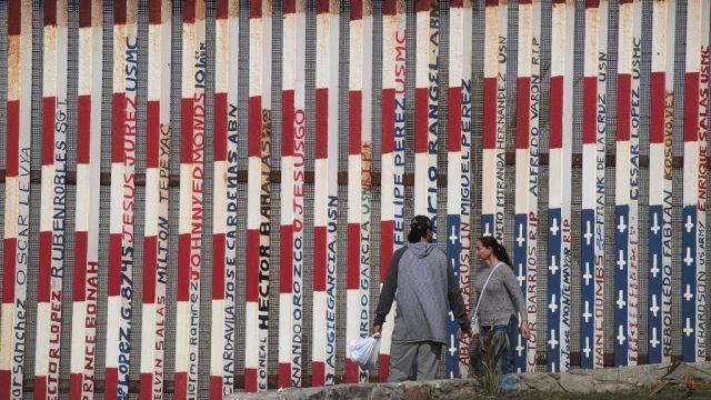 Foto: Dos personas caminan a lado de la valla fronteriza entre Tijuana y San Diego el 28 de enero del 2019