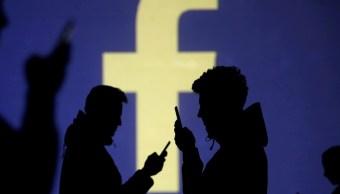 Foto: Silueta de usuarios con teléfonos celulares junto a una proyección de pantalla del logotipo de Facebook, 28 de marzo de 2018 (Reuters)