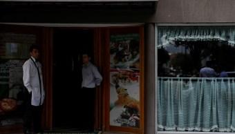 Foto: Trabajadores se paran en la puerta de un restaurante durante un apagón en Caracas, Venezuela, el 7 de marzo de 2019