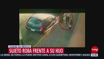 Hombre roba artículos de un auto, acompañado por su hijo