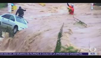 Rescatan a hombre atrapado en auto durante inundación