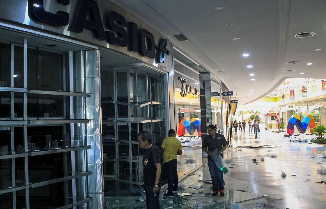 Varias personas observan los daños en locales del centro comercial Sambil en Maracaibo, Venezuela, 14 marzo 2019