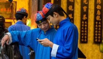 Foto: Dos camareros utilizan sus teléfonos inteligentes mientras trabajan, marzo 16 de 2019 (Getty Images)