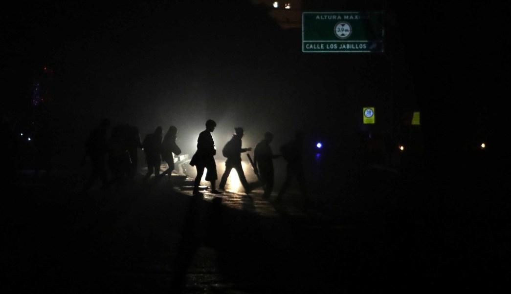 Foto: Transeúntes en una calle a oscuras por el apagón eléctrico en Caracas, 9 marzo 2019