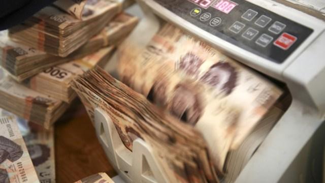 Foto: Los billetes de quinientos pesos mexicanos se procesan a través de una máquina de conteo dentro de una tienda de cambio de divisas en la Ciudad de México, abril 16 de 2019 (Getty Images)